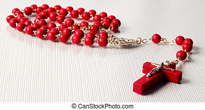 Red Italian rosary on the white reflective background. Diagonally placed cross in focus, the rest of rosary out of focus
