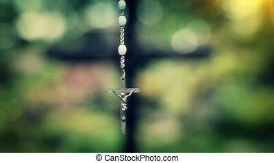 Rosary slowly swinging on green background