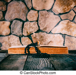 rosary with a crucifix on an open old book on old wooden table on a background of stone walls. with space for your text