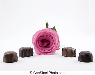 Photo of a pink rose and several pieces of chocolate by it
