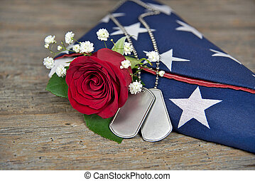 rose and dog tags on flag - Military dog tags and red rose...