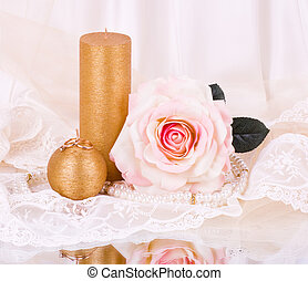 rose and golden candle with beads