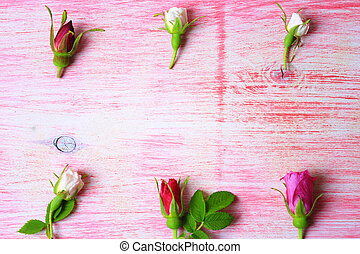 rose buds on a pink wooden background in retro style shabby chic top view