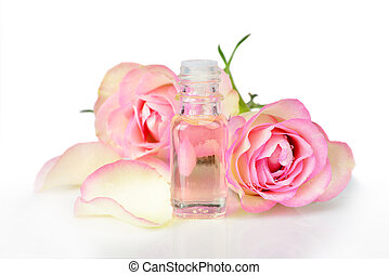 Rose essential oil - Vial with essential oil and two roses ...