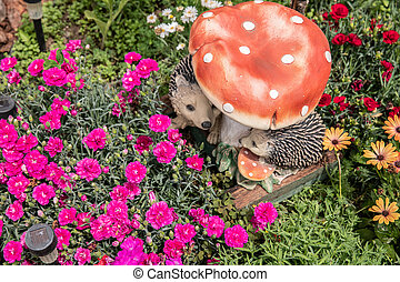 rose flowers in the garden and decorative hedgehogs.
