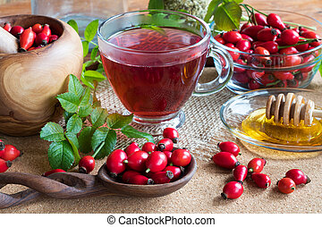 Rose hips and rose hip tea on a wooden table