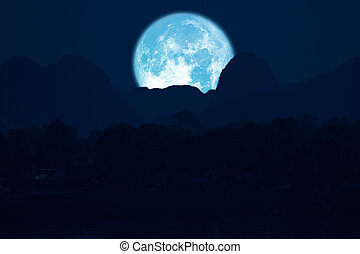 rose moon on night sky back over silhouette mountain