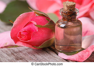 Rose oil and pink beautiful flower on wooden table