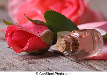 Rose oil in a glass bottle and pink flowers on wooden table