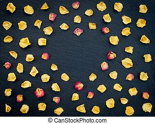 Rose petals heart frame on black background