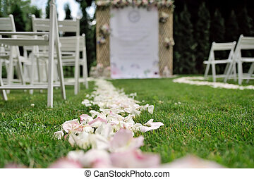 Rose petals on grass, in front of beautiful wedding trellis