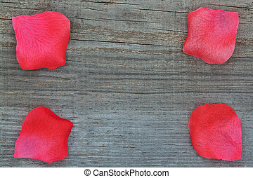Rose petals on the wooden texture. Close-up.