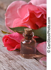 Rose water in a glass bottle on a background of pink roses