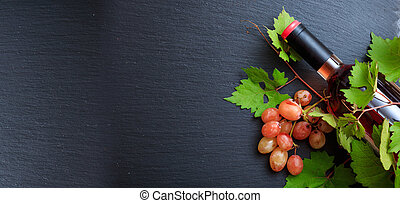 Rose wine bottle and fresh grape leaves on black background, top view, copy space