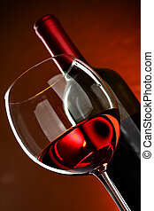 Rose wine - Glass and bottle of wine over red background
