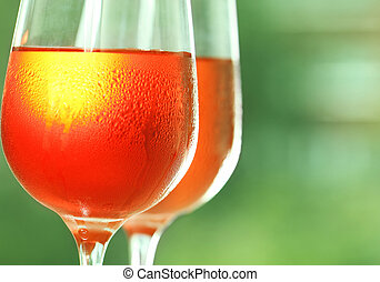 Rose wine - Two glasses of a rose wine against green...