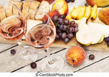 Rose wine - Two glasses of rose wine and board with fruits,...