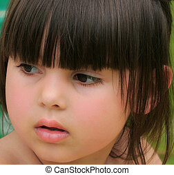 Face of a little girl with rosebud shaped lips.