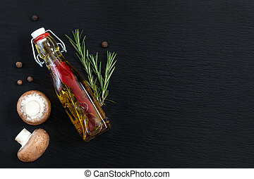 Rosemary bunch, mushrooms, olive oil and pepper on black...