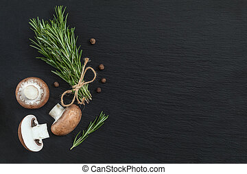 Rosemary bunch of bouquets, mushrooms and fragrant pepper on black stone surface. Top view, copy space.