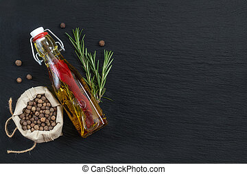 Rosemary bunch, olive oil and pepper on black stone surface