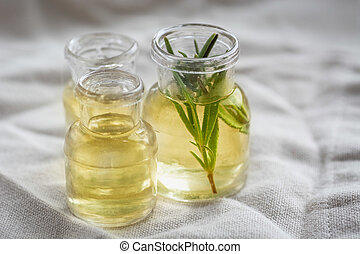 Rosemary essential oil in small bottles with a fresh rosemary inside closeup