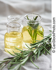 Rosemary essential oil in small bottles with a fresh rosemary twig closeup