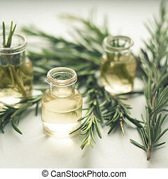 Rosemary essential oil in small bottles with a fresh rosemary twigs closeup, selective focus