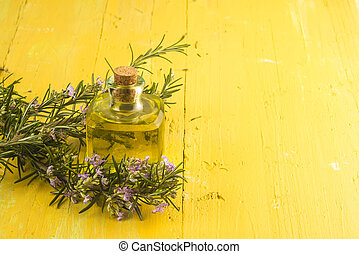 Rosemary essential oil in small glass bottle and plant with ...