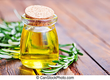 rosemary oil in glass bottle and on a table