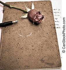 roses and a fountain pen on an old scrapbook