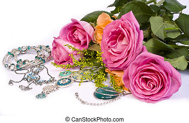 Roses and jewellery on white background
