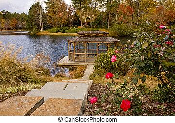 A beautiful rose garden by a gazebo and a lake