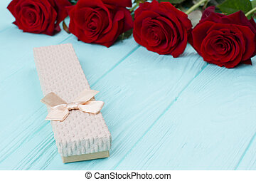 Roses and little gift box. Flowers and box with jewelry on...