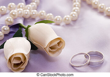 roses and wedding rings over satin