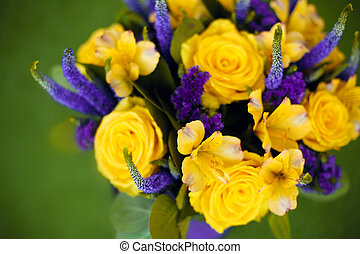 Roses bouquet of flower gift close up, yellow violet color flowers isolated on green grass background. View top