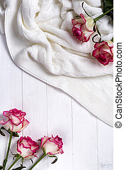 Roses frame with plaid on wooden white background
