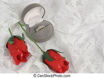 a diamond ring and silk roses on lace - room for text