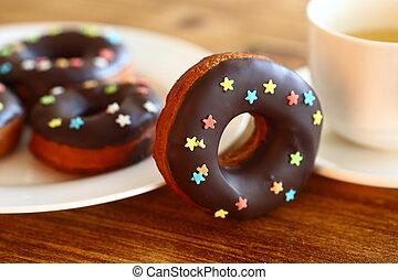 rosquilla, de, pastel, con, chocolate, y, azúcar, estrellas, sobre la mesa, con, taza del té