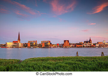 Cityscape image of Rostock riverside with St. Peter's Church during summer sunset.