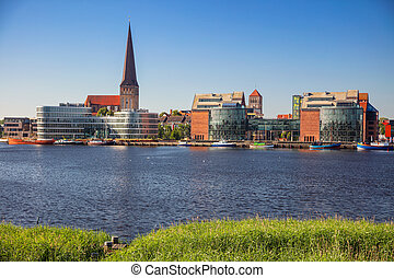 Cityscape image of Rostock riverside with St. Peter's Church during sunny summer day.