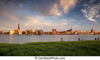 Panoramic cityscape image of Rostock riverside with St. Peter's Church during summer sunset.