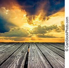 Rostrum made of wooden planks on sky before sunset