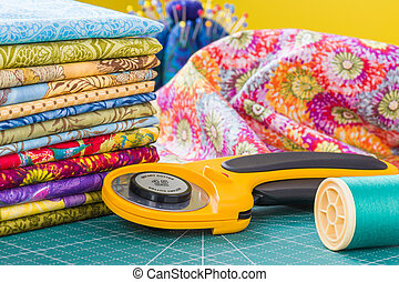 Rotary cutter and spool of thread on a background fabric