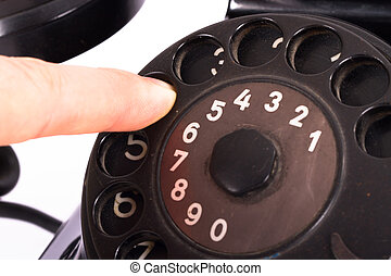 Rotary Dial of Vintage Phone - Close up view, hand finger on...