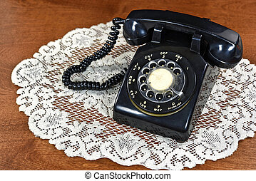 rotary dial telephone on lace doily