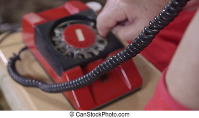 Female finger dialing 911 emergency call on rotary phone, focus on cord