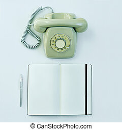 rotary telephone, pen and blank notepad on a table -...