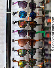 Rotatable rack with colorful sunglasses in market.