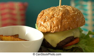 Rotate homemade burger with fried potatoes and sauces on a...